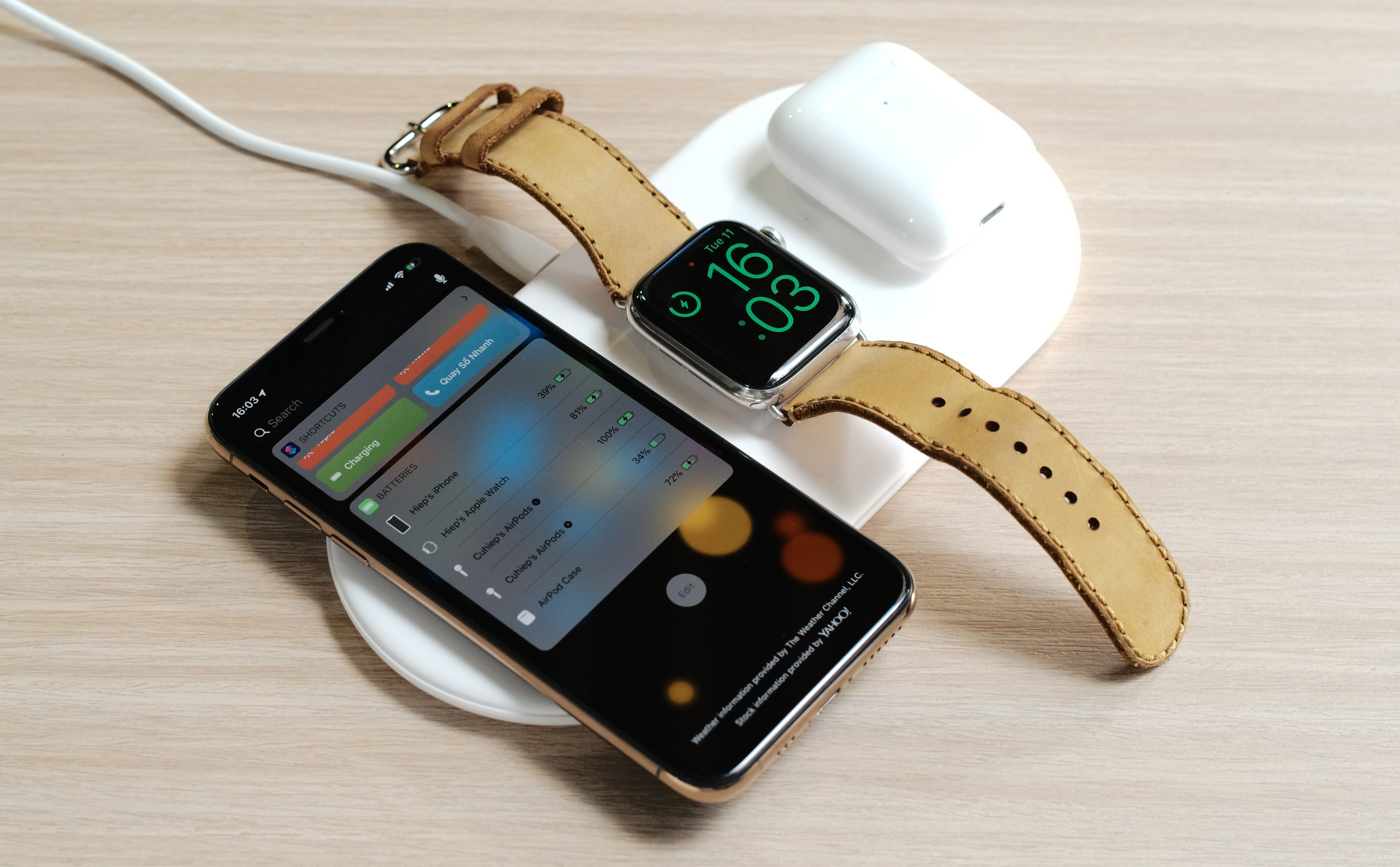 On the hands of 3-way wireless charger iPhone, Airpods and Apple Watch of Baseus