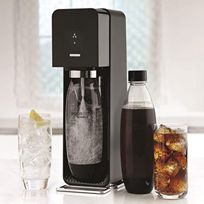 a SodaStream Source Sparkling Water Maker in black with a bottle of cola and two glasses of soda