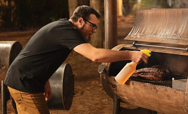 aaron franklin spraying meat in a bbq smoker