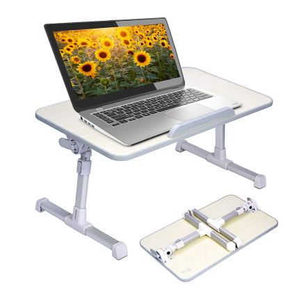 a neetto folding bed tray table sitting upright on a flat surface with a laptop sitting on top of it on a white background