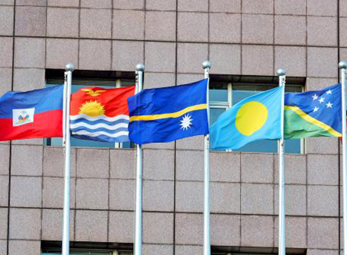 The Kiribati flag (second from the left) and the Solomon Islands flag (rightmost) at the Taiwan Diplomatic Office on 2 September. Photo Taipei Times.