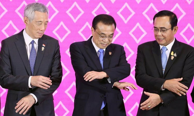 Chinese Premier Li Keqiang (middle) shakes hands with Singapore Prime Minister Lee Hsien Loong (left) and his Thai counterpart Prayut Chan-ocha at the 35th ASEAN Summit in Bangkok, Thailand today. Photo: Reuters.