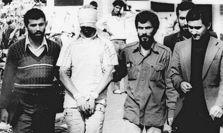 A human hostage (blindfolded) blindfolded and tied hands at the US embassy in Tehran in 1979. Photo: IPM.