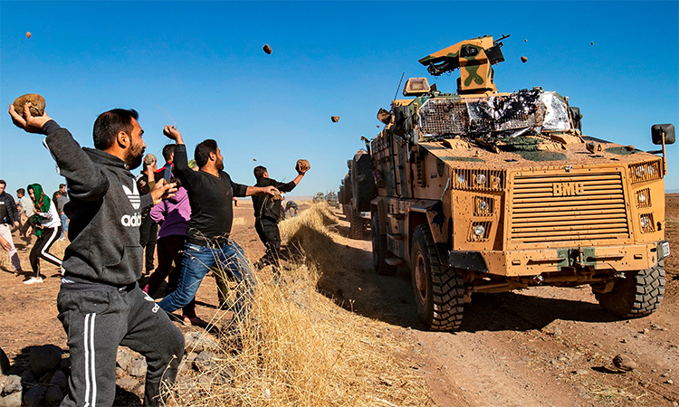 Kurdish villagers throw stones at Turkish armies patrolling with Russian military police near the Syrian town of al-Maabadah, Syria on November 8. Photo: AFP.