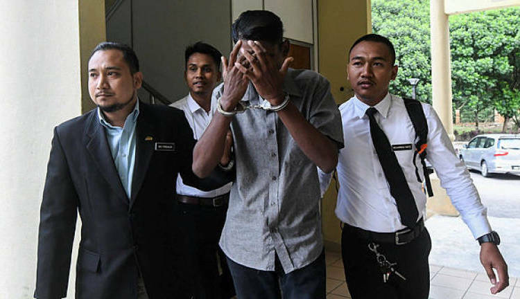 K. Ganesh covered his face with his hand in Selayang court, Selangor state, Malaysia on November 5. Photo: Bernama.