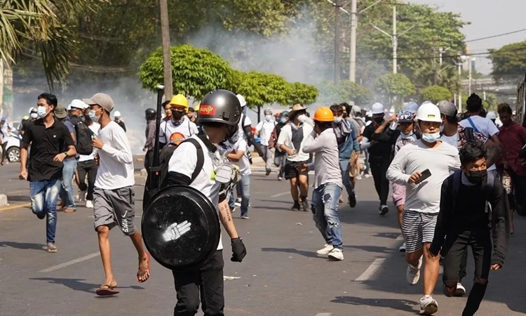 Protesters in Yangon fled after being shot with tear gas and rubber bullets on February 28 by police.  Photo: Nikkei.